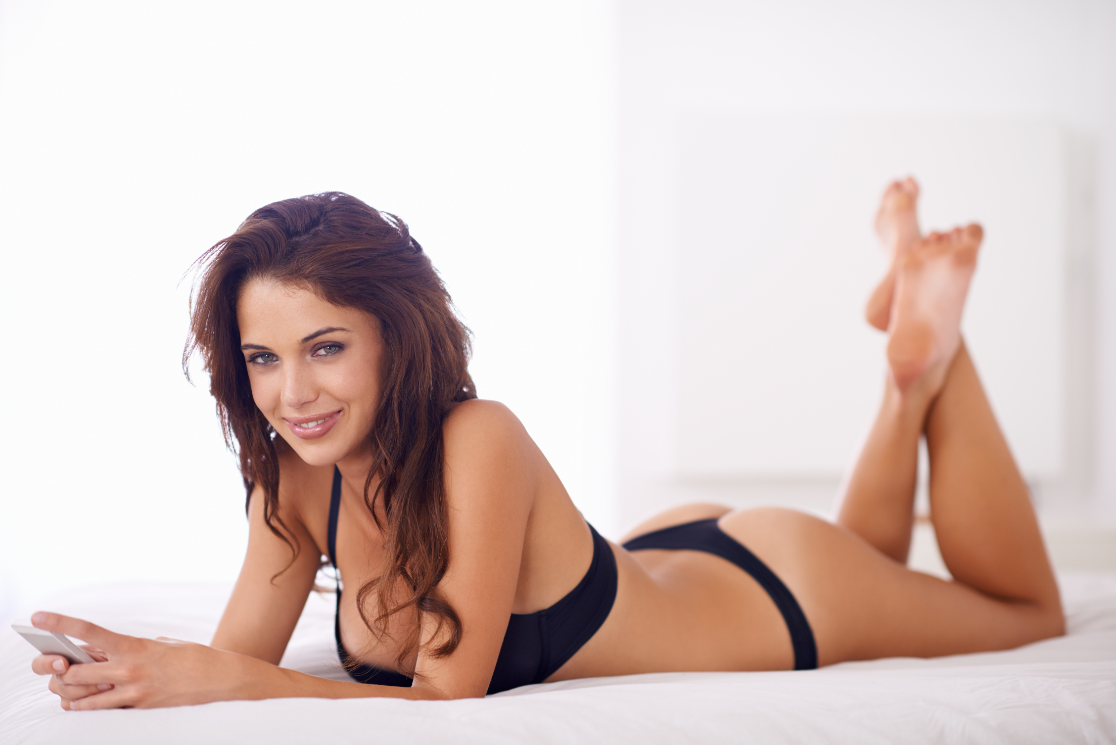 A young woman in her underwear sending a text message while lying on the bed